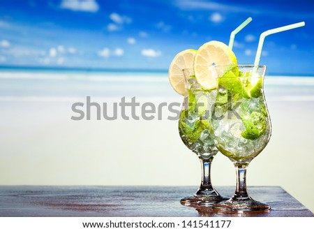 Mojito cocktail with lime and mint on a beach background - stock photo