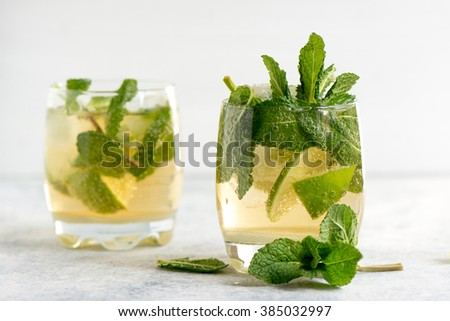 mojito cocktail with rum, lime and soda, garnished with mint - stock photo