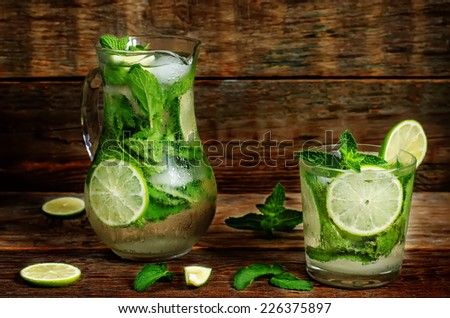 Mojito on a dark wood background. toning. selective focus on the mint in the glass. - stock photo