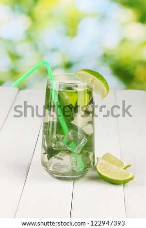 Mojito on wooden table on bright background - stock photo