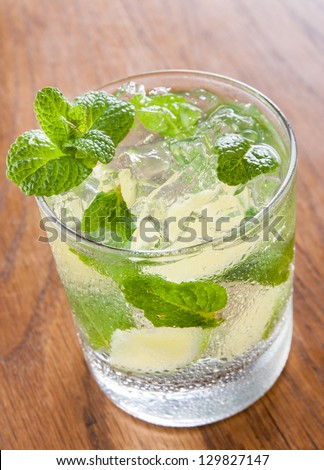 Mojito served in a glass with crushed ice and lime on wooden table - stock photo