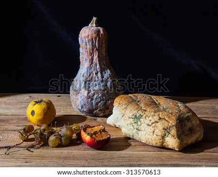 Moldy and rotten food on a wooden table - stock photo