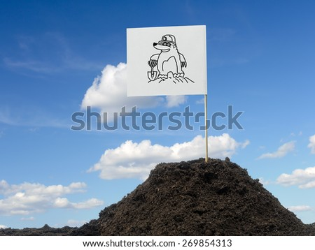 Mole mound with white flag showing mole icon affixed over blue sky - stock photo