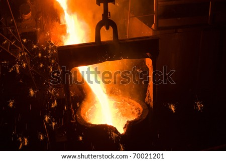 Molten metal poured from lathe for iron casting. - stock photo