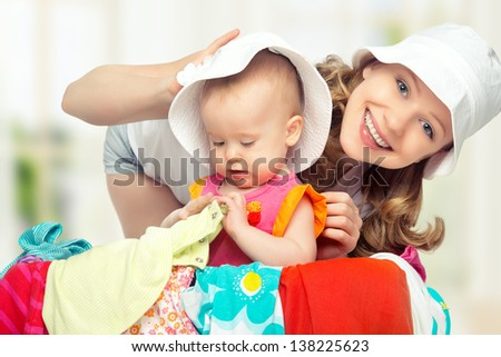 Mom and baby girl with suitcase baggage and clothes ready for traveling on vacation - stock photo