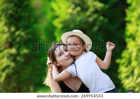 Mom and baby little girl on the blurry background of fresh juicy summer greens. Happy family. - stock photo