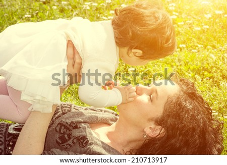 mom and baby lying in the grass - stock photo