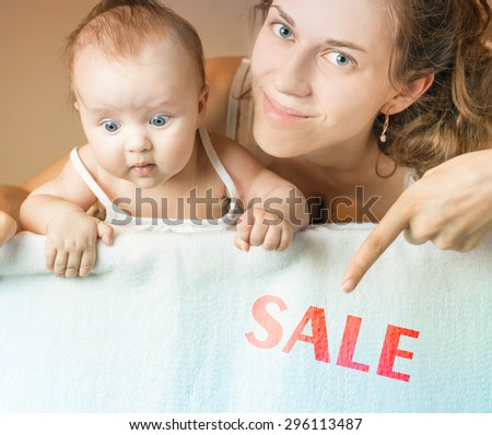 Mom and baby lying on white blanket. Advertising banner sign - Mom is pointing down on text with word discount. Child stares down at inscription. Mother smiling and looking at camera - stock photo