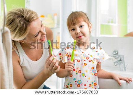 mom and child daughter brushing teeth in bathroom - stock photo