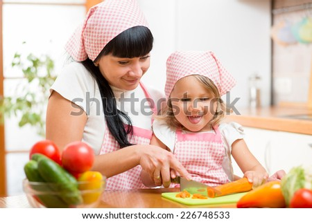 mom and child daughter preparing healthy food at kitchen - stock photo