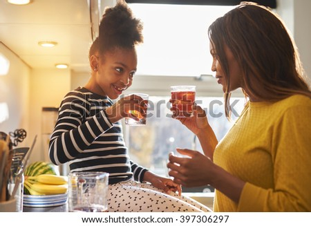 Mom and child in kitchen drinking lemonade, happy smiling family - stock photo