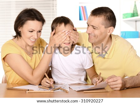 mom and dad and son do homework together - stock photo