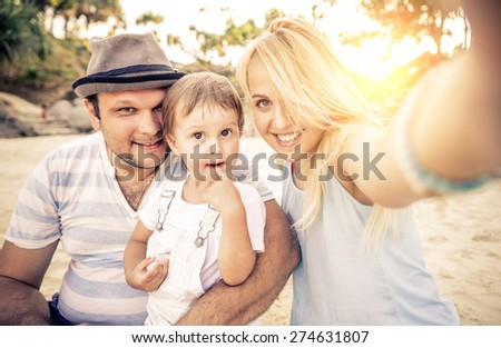Mom and dad playing with their handsome son - Family and baby outdoors - Young beautiful mother taking a self portrait with her family - stock photo