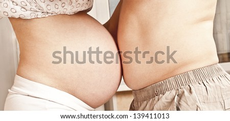 Mom and Dad touch each other with their bellies - stock photo