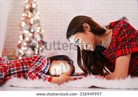 Mom and daughter are waiting for New Year presents near the Christmas tree. - stock photo