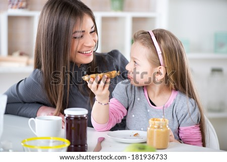 Mom and daughter breakfast in the kitchen environment and talking. Cute little girl eats bread with peanut butter. - stock photo