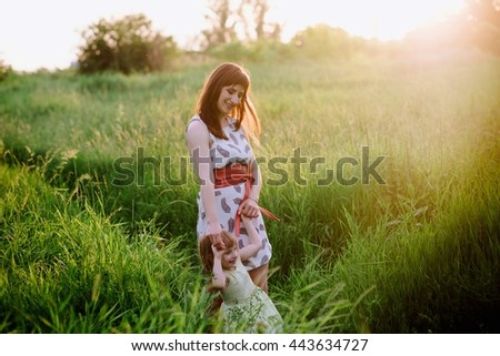 Mom and daughter dancing in nature together in sunset light, the family, motherhood, entertainment, recreation, game - stock photo