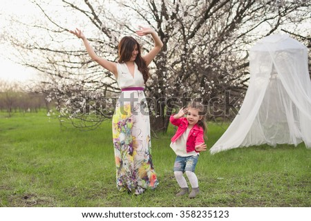 Mom and daughter dancing in nature together, the family, motherhood, entertainment, recreation, game - stock photo