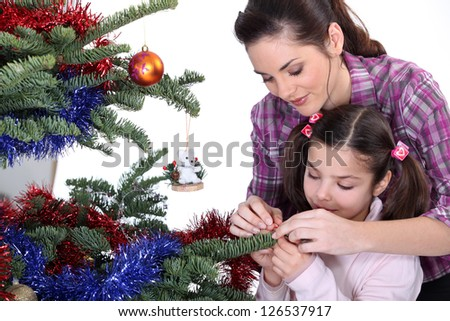 Mom and daughter decorating the Christmas tree - stock photo