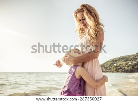 mom and daughter embracing on the beach. concept about family - stock photo