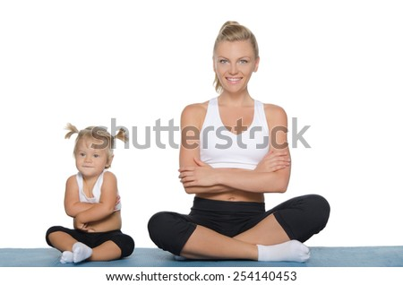 Mom and daughter engage in fitness on blue mat - stock photo