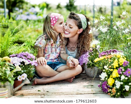 Mom and daughter have fun in the work of gardening - stock photo