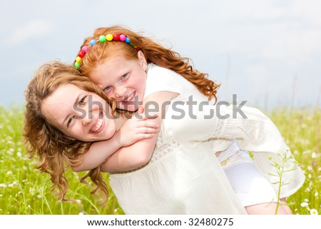 Mom and Daughter Having Fun in the field. Focus on eyes. - stock photo