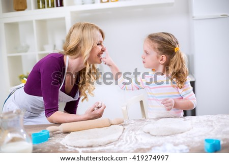 Mom and daughter having fun in the kitchen while they are making dough - stock photo