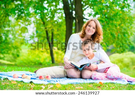 Mom and daughter in the park reading a book - stock photo