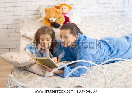Mom and daughter in the same blue terry robe reading a book - stock photo