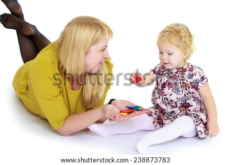 Mom and daughter lying on the floor and playing educational games, Montessori school. Isolated on white background studio photo. - stock photo