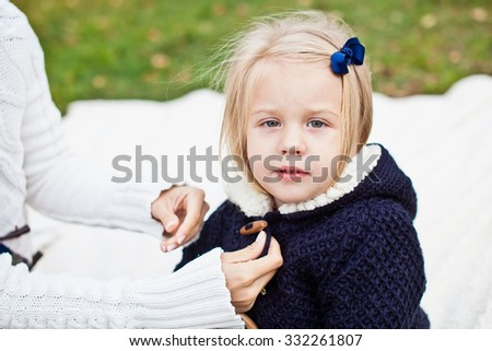 Mom and daughter on picnic in park. Mother change kid clothes to warm and cozy sweater because of cold autumn weather. Infant in blue cardigan and woman in white jumper. Diversity and family concept - stock photo