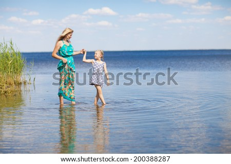 mom and daughter on the lake - stock photo