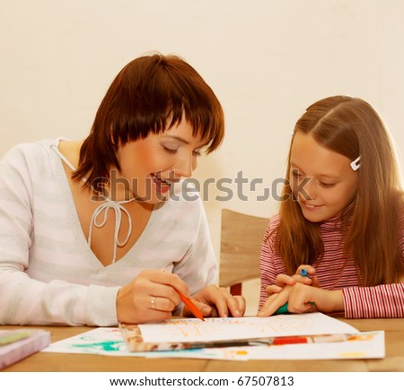 Mom and daughter painting on paper. Happy family. - stock photo