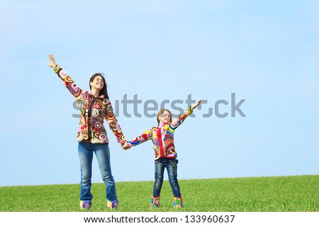 Mom and daughter play in the field - stock photo