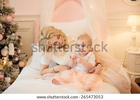 Mom and daughter playing on the bed, hugging - stock photo