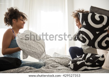 Mom and daughter playing with pillows in a bedroom. - stock photo