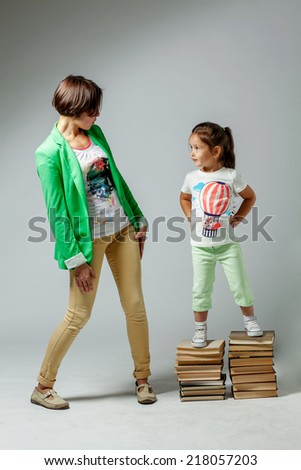 Mom and daughter standing on a pile of books - stock photo