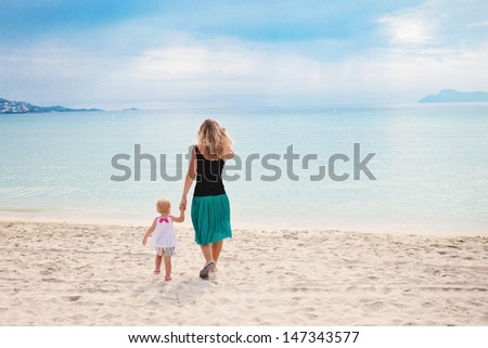 mom and daughter walking at the beach - stock photo