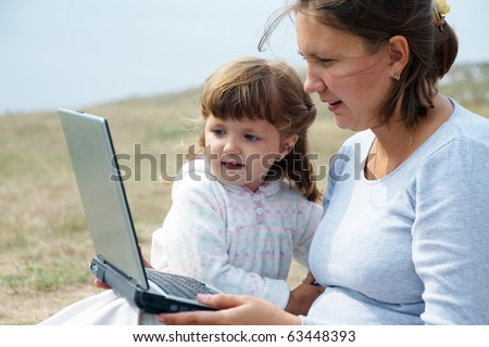 Mom and daughter working on laptop outdoors - stock photo