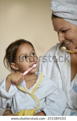 Mom and her little daughter brushing their teeth - stock photo