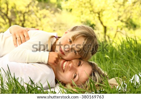 Mom and her little daughter lie on the grass - stock photo
