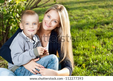 Mom and her son enjoyed the walk, sitting on the grass - stock photo