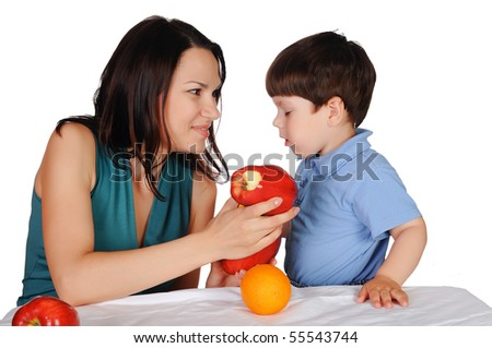 Mom and her young son together eat fruits - stock photo