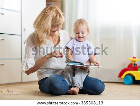 mom and kid boy reading a book at home - stock photo
