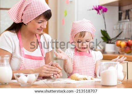 Mom and kid girl preparing cookies together at kitchen - stock photo
