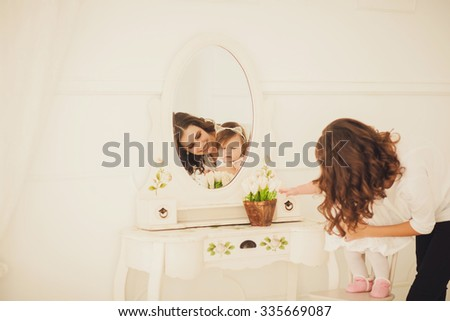 mom and kid playing in a bright room. - stock photo