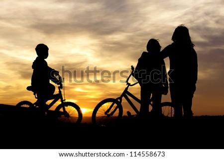 Mom and kids bond at sunset. - stock photo