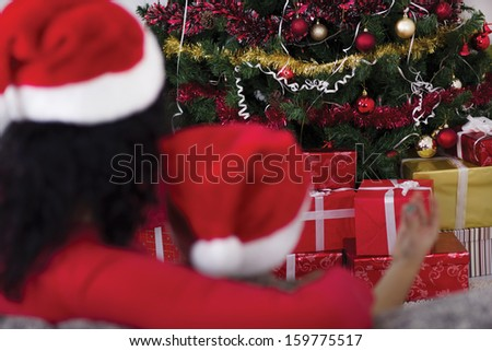Mom and son embracing, looking at the Christmas tree - stock photo