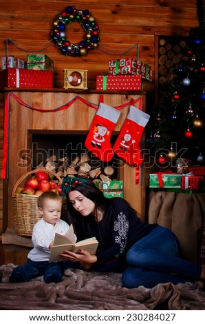 Mom and son reading a book in a Christmas setting - stock photo